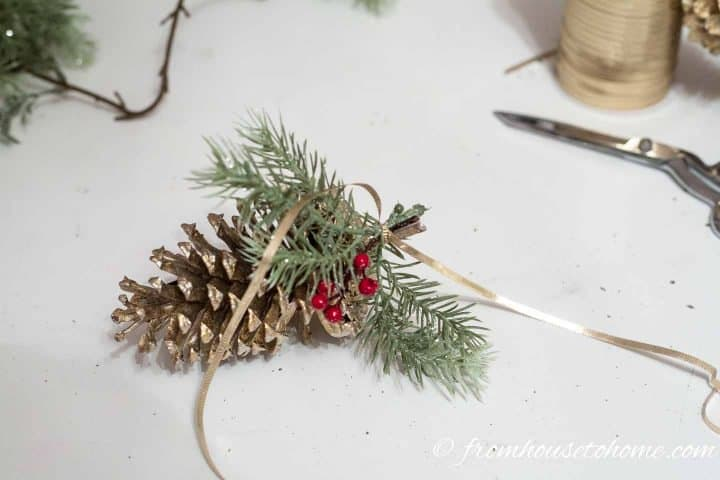 Evergreen and berries tied onto pine cone with gold ribbon