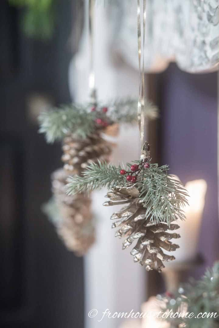 Evergreens and berries on pine cone DIY Christmas ornaments