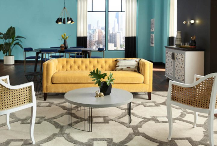 "Living room with yellow sofa and walls painted with the HGTV Home by Sherwin Williams color of the year ""Reflecting Pool"""