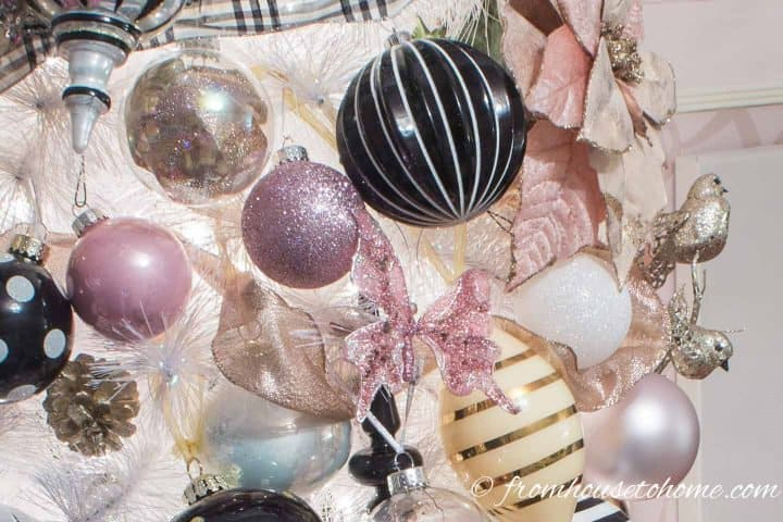 White Christmas tree with pink, black and white ornaments including a pink butterfly