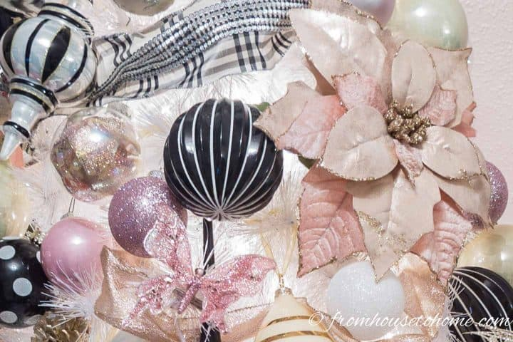 Pink and black and white ornaments on a white Christmas tree