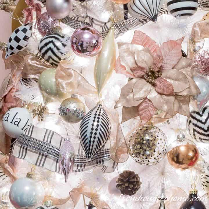 Black and white ornaments with pink ornaments and back and white ribbon on a Christmas tree