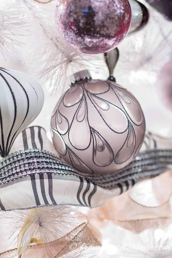 Close up of black and white ornaments and ribbon on a Christmas tree