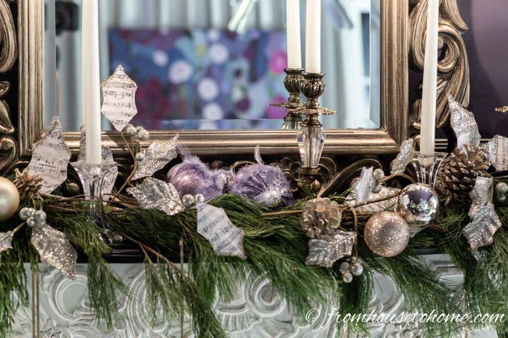 Evergreen branches with white candles, pine cones and purple Christmas ornaments on a fireplace mantel