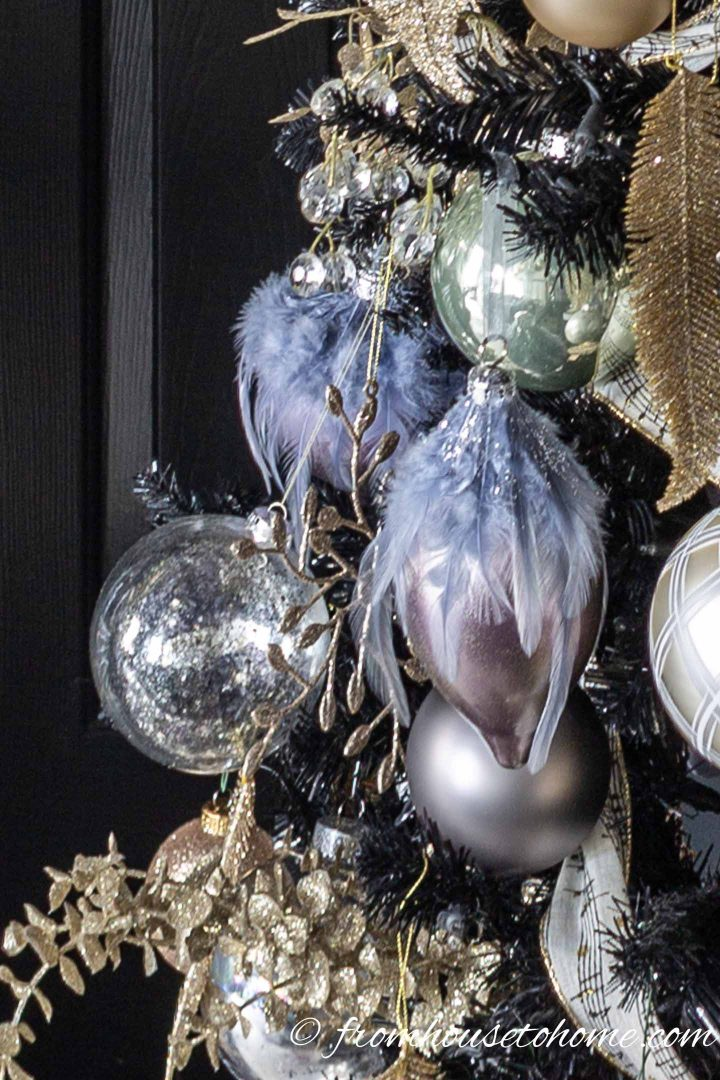 Purple and gold Christmas ornaments on a black Christmas tree