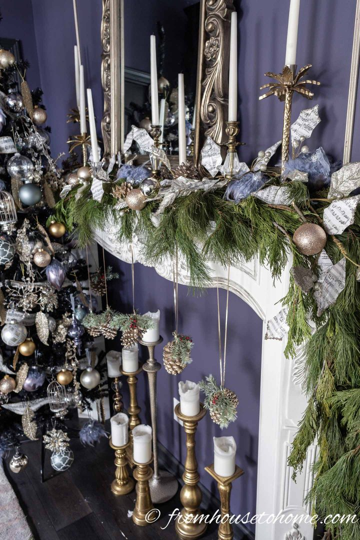 Fireplace mantel decorated with evergreens, candles and purple Christmas ornaments