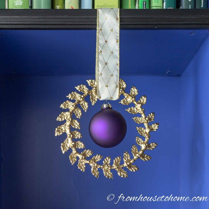 Gold wreath Christmas ornament with a purple Christmas ornament hung from a shelf with ribbon