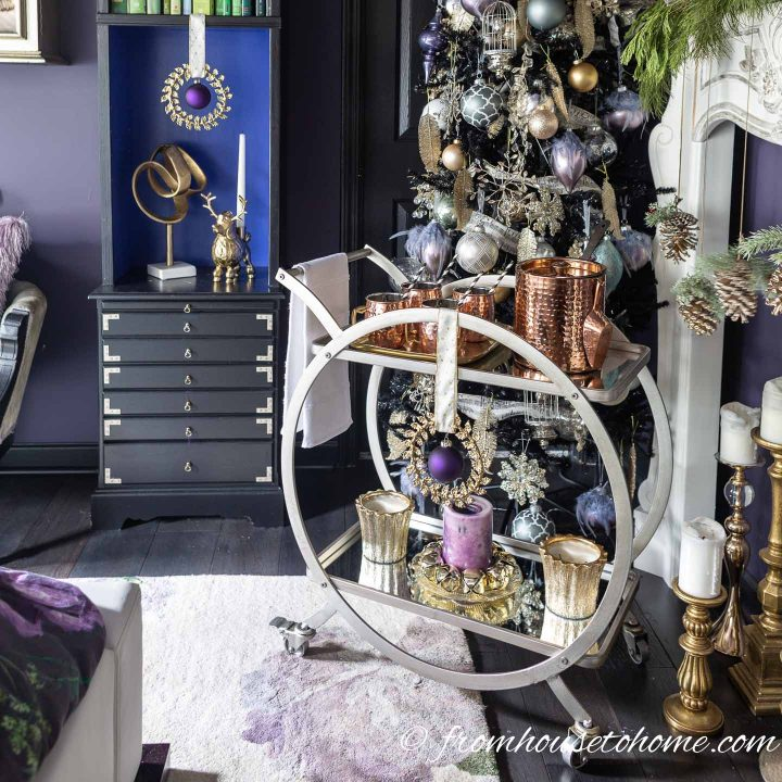 Hot apple cider bar with purple and gold Christmas decorations on a bar cart