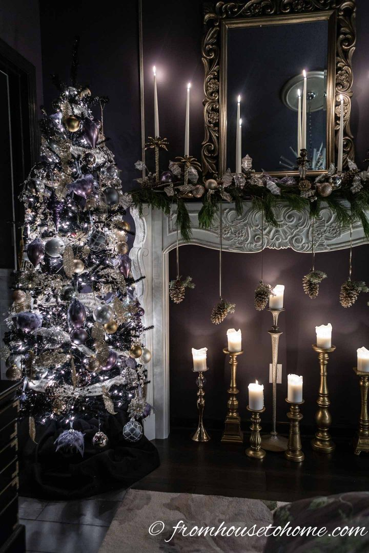 Purple and gold Christmas tree beside a fireplace mantel with pine cones and candles