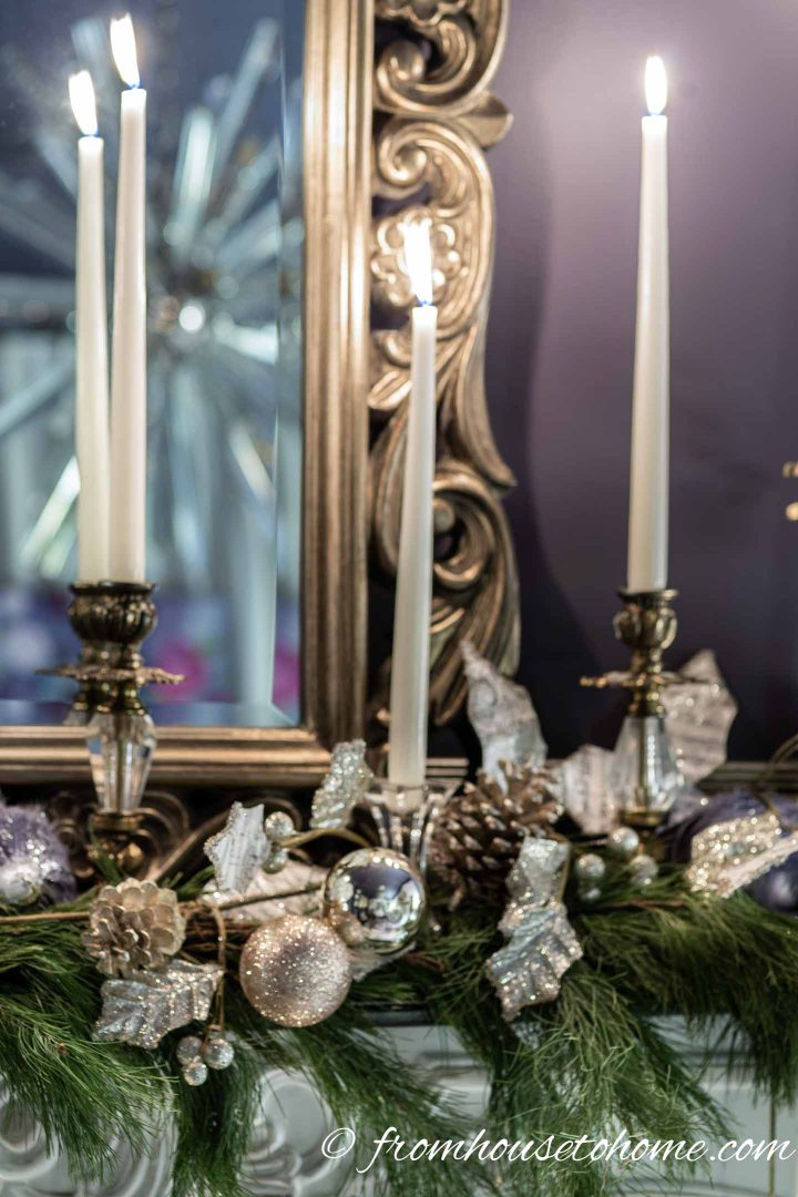 Mantel Christmas decorations with white candles, gold ornaments, pine cones and evergreen branches