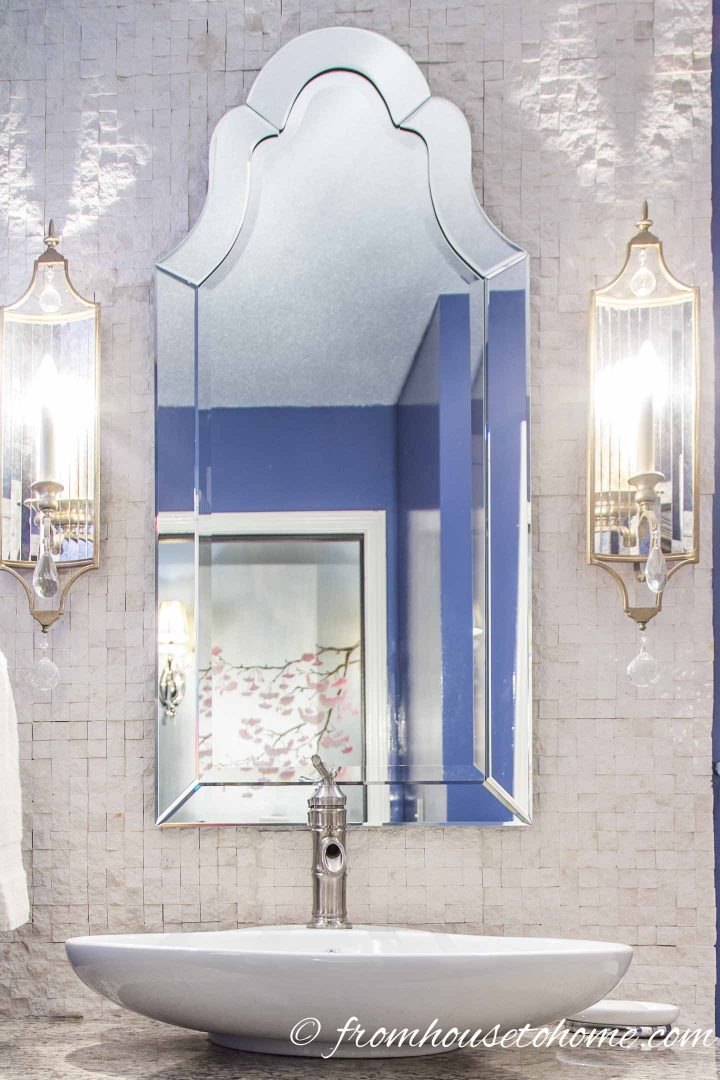 Venetian style mirror above a basin sink in a glamorous guest bathroom