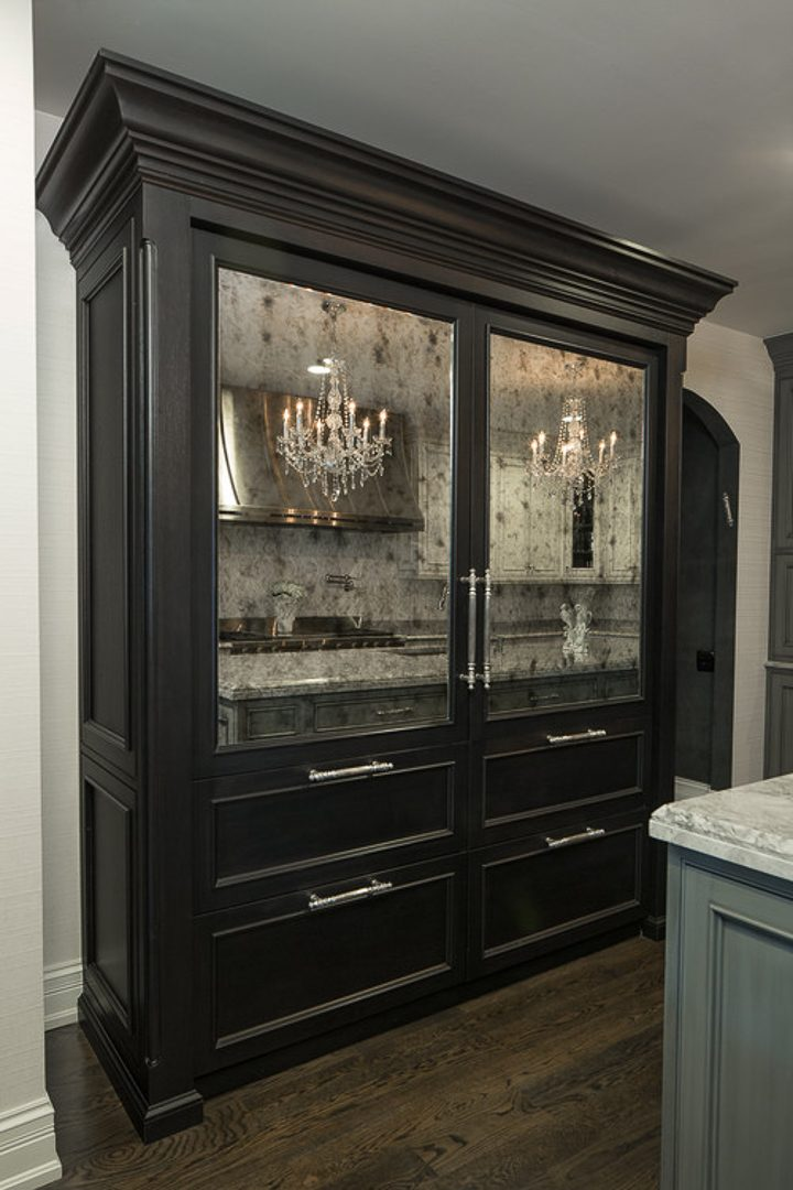 Aged mirrors on the front of armoire doors in a Hollywood glam kitchen