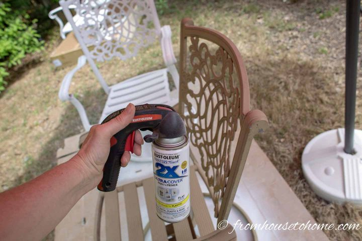 Spray can being held about 6 inches from a metal patio chair