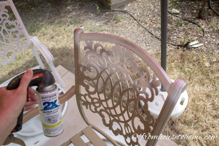 A metal outdoor chair being spray painted