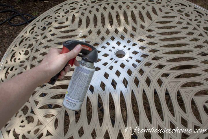 A metal patio table being spray painted white
