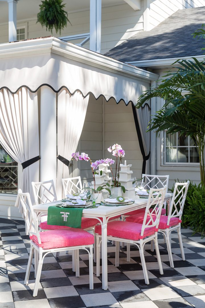 White outdoor dining table with pink cushions and white and black outdoor curtains