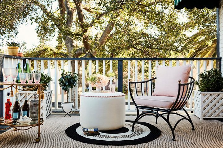 Gold bar cart, white outdoor pouf, black and white outdoor rug and black outdoor chair with a pink cushion