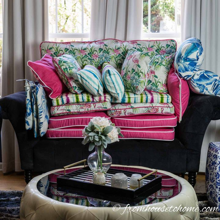 Palm Beach chic outdoor decor cushions piled up on a sofa