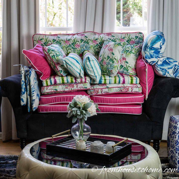 Palm Beach chic outdoor decor cushions piled up on a sofa