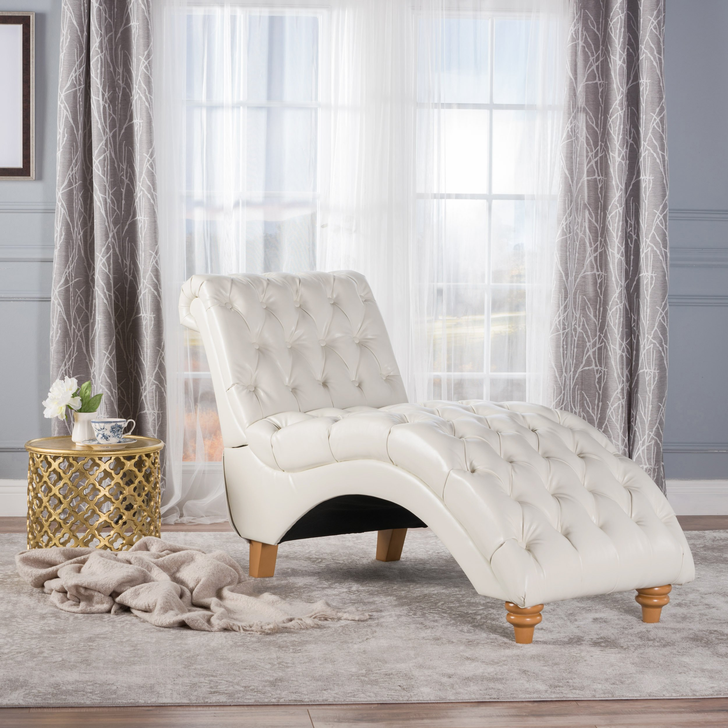 White leather chaise with a gold side table
