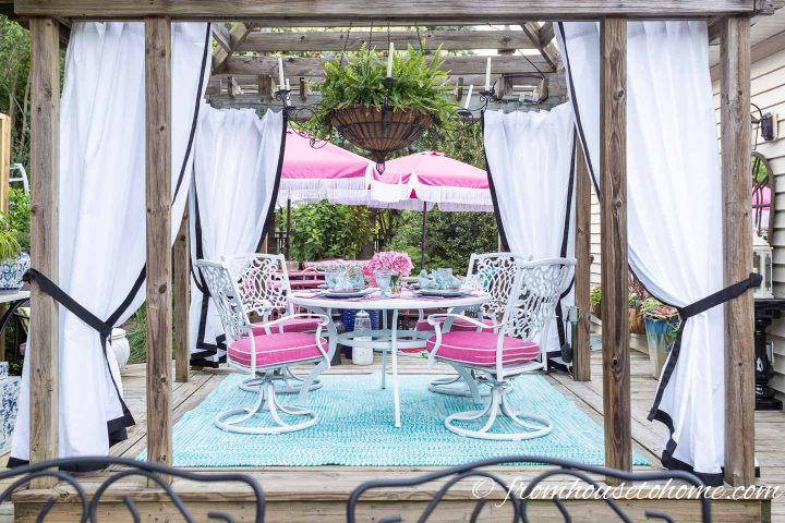 White DIY outdoor curtains with black edges hung in a gazebo
