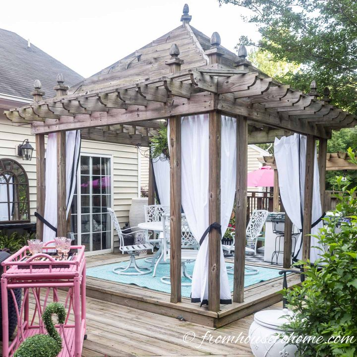 Gazebo with white DIY outdoor curtains and black edges