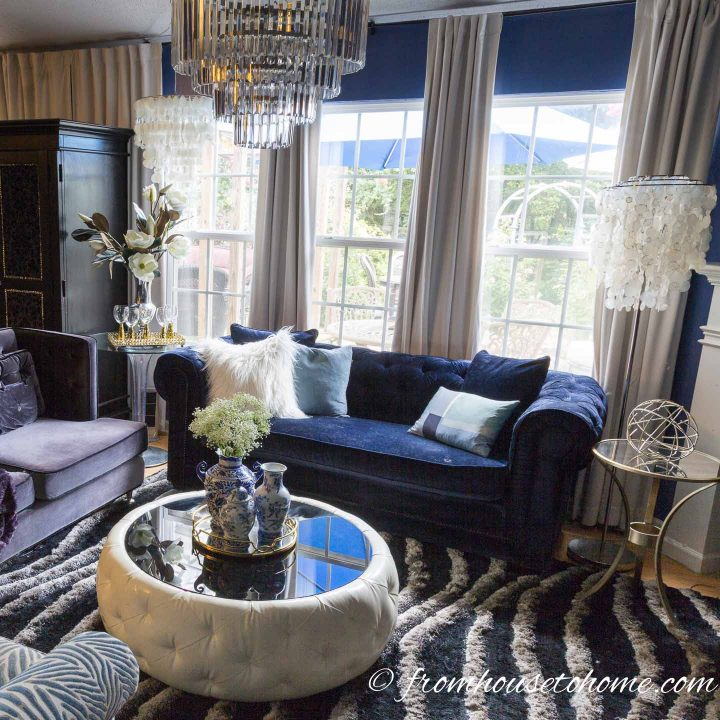 Living room with multiple pendant lights over a round coffee table and blue velvet sofa