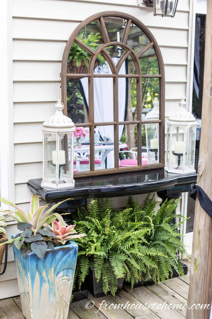 A garden mirror hung on a house wall above a black outdoor console table