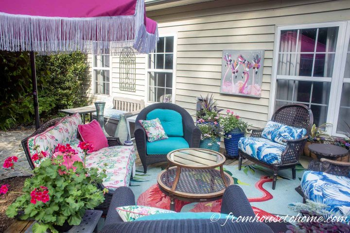 Deck makeover with pink and turquoise cushions on outdoor furniture and flamingo art hung on the wall