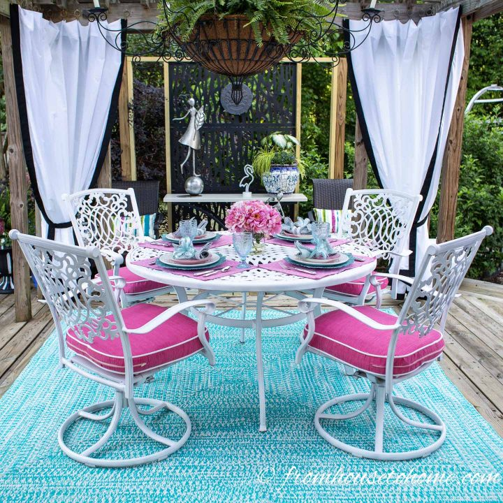 Painted white outdoor dining table and chairs with pink cushions and a turquoise area rug in a gazebo with white and black outdoor curtains