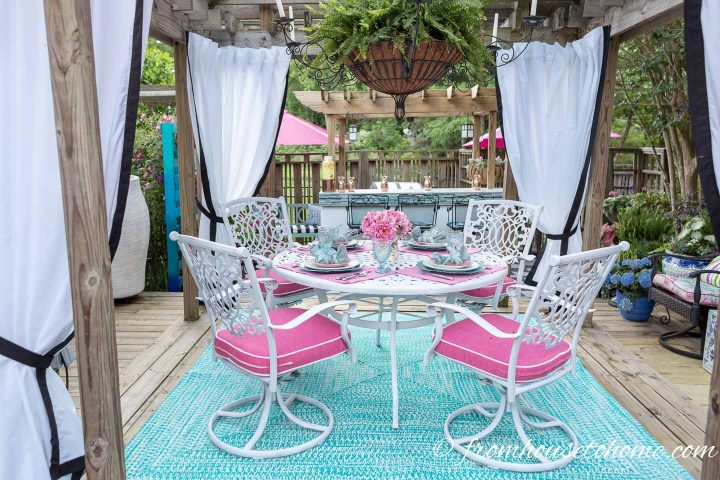 White outdoor patio furniture set with pink and turquoise place settings in a gazebo with white outdoor curtains