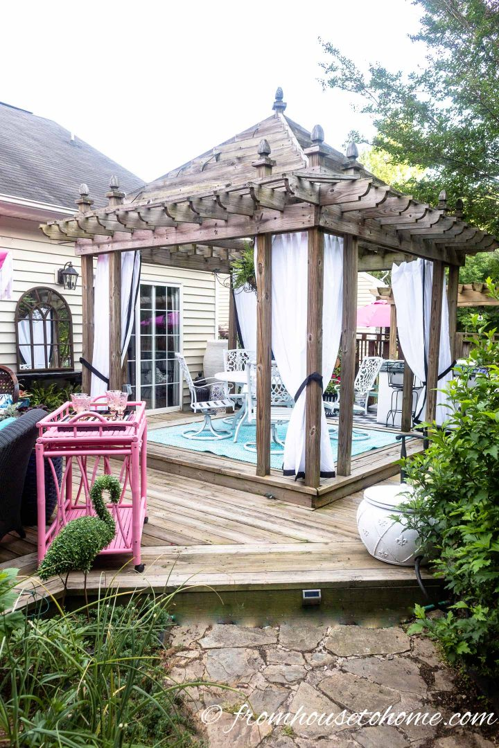 Gazebo with curtains on the deck and a flamingo topiary
