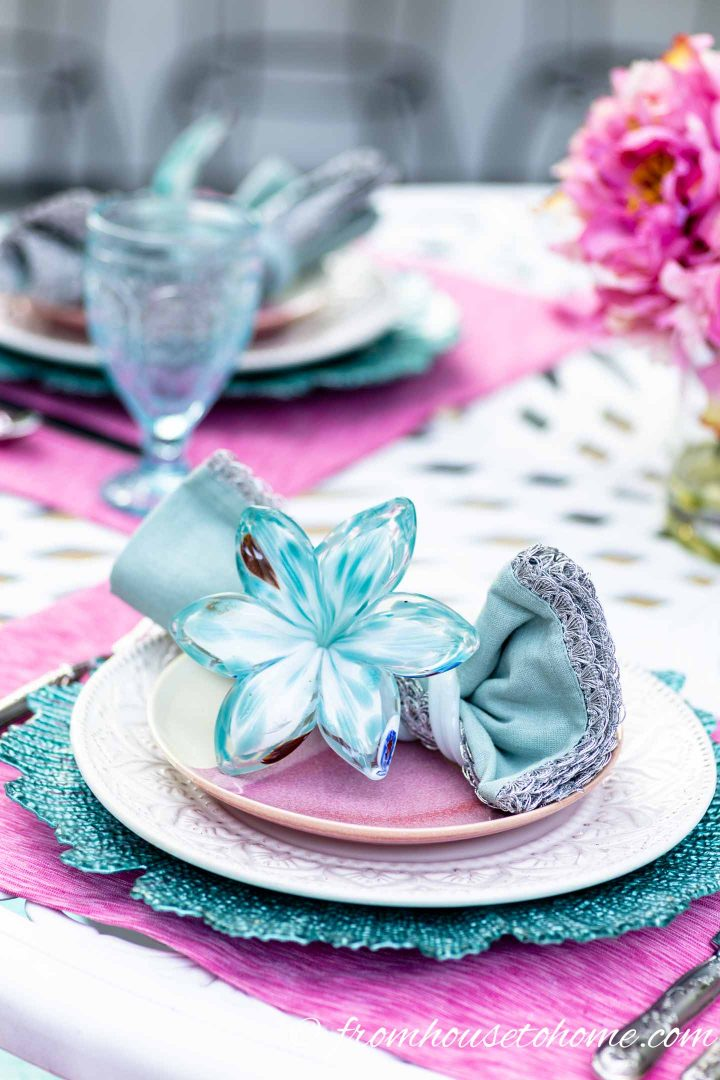 Palm Beach chic turquoise and pink place setting on a white outdoor table