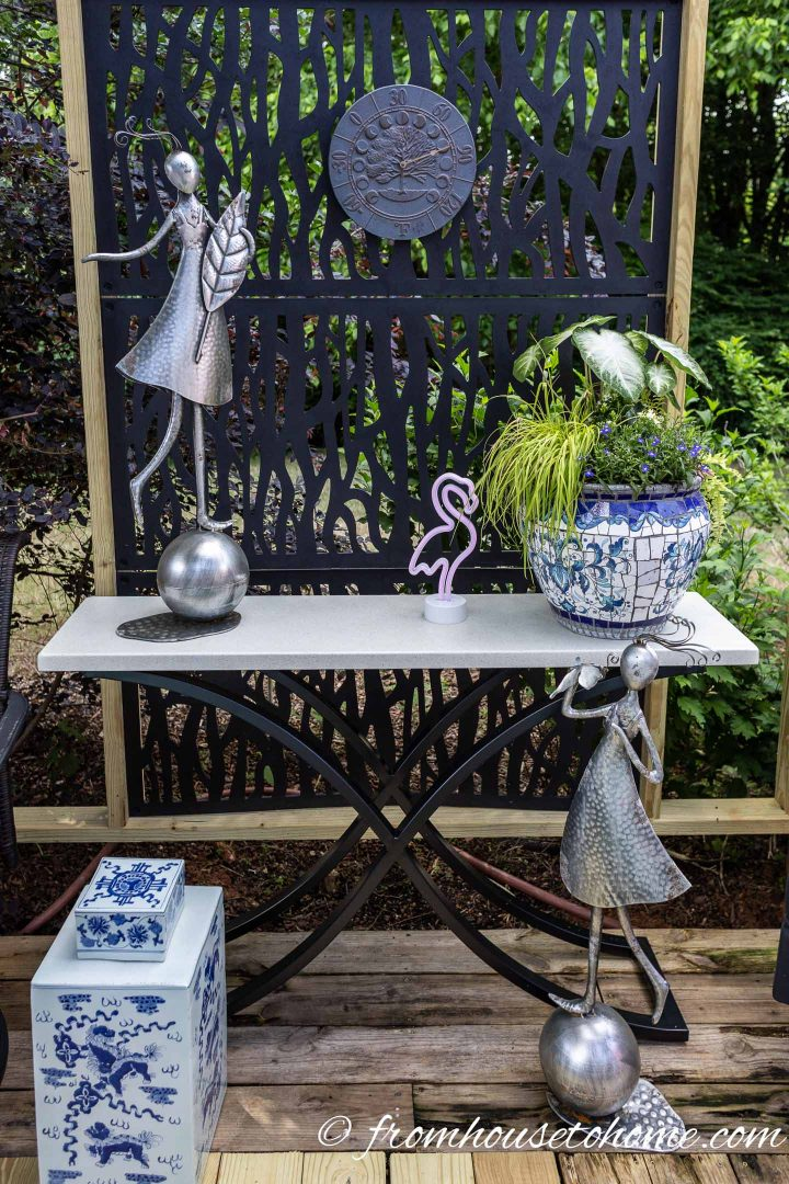 Silver garden statues, blue and white ginger jar and a white console table in front of the privacy screen on the deck