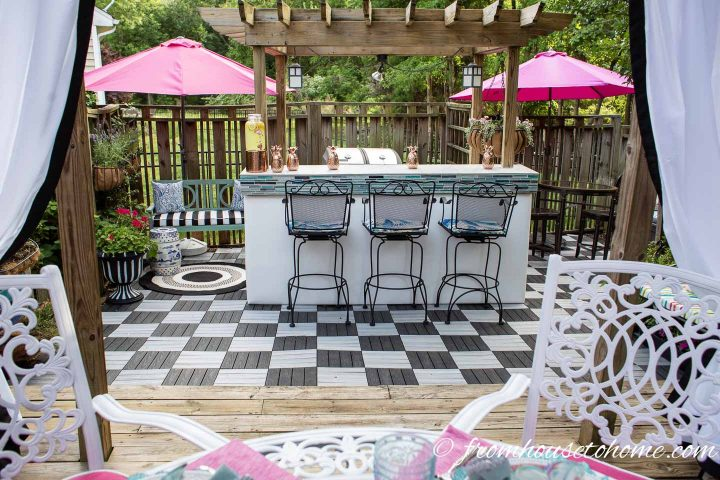 Glam outdoor bar with white vinyl front, turquoise glass tiles and black and white checkerboard deck tiles