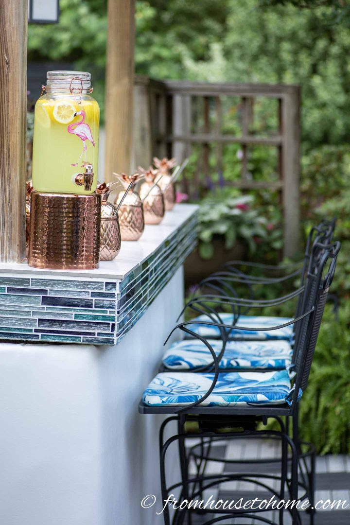 Outdoor bar with white vinyl front, turquoise glass tiles and black wrought iron bar stools