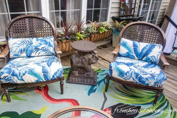 Blue and white cushions with palm fronds on outdoor rattan furniture