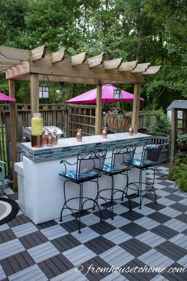 Outdoor bar with a pergola and black and white deck tiles