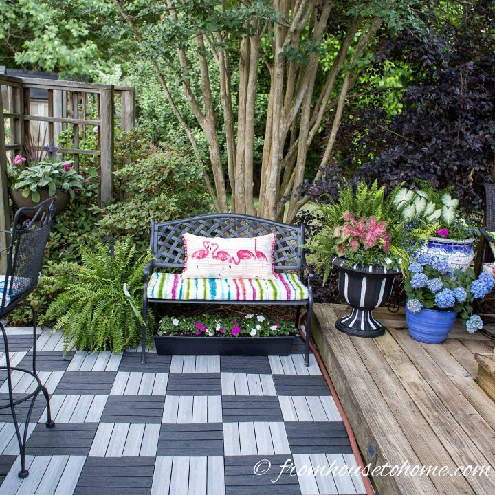 Black metal outdoor bench with colorful striped cushion and planter boxes