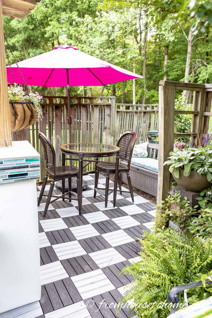 Black and white deck tile patio with bistro table and pink umbrella