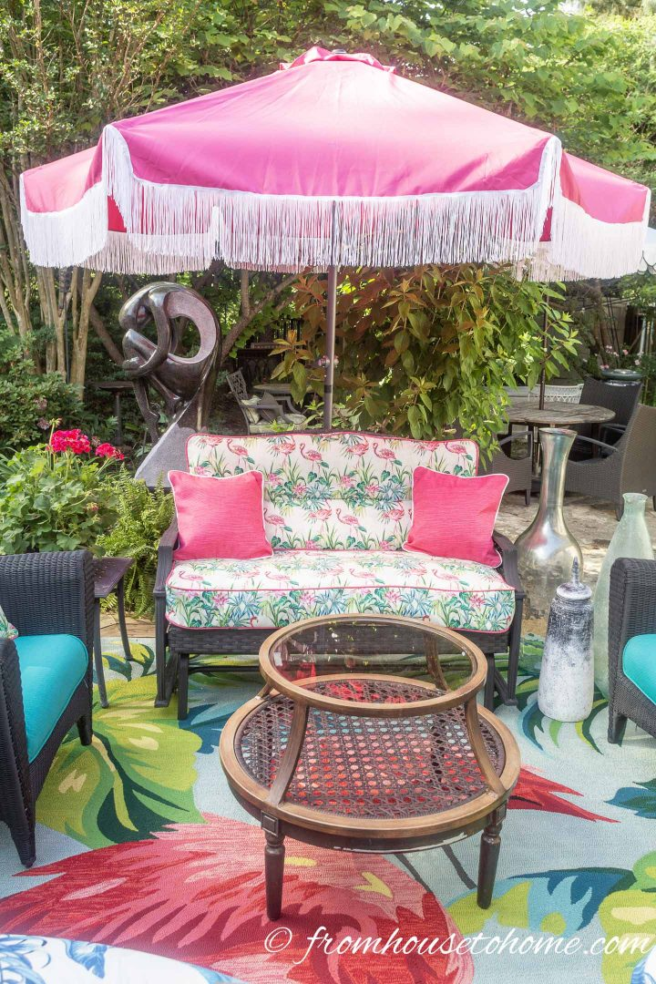 Fuchsia patio umbrella with white fringe over an outdoor sofa with flamingo cushions