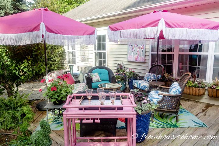 Two pink and white patio umbrellas with a pink outdoor bar cart on a deck