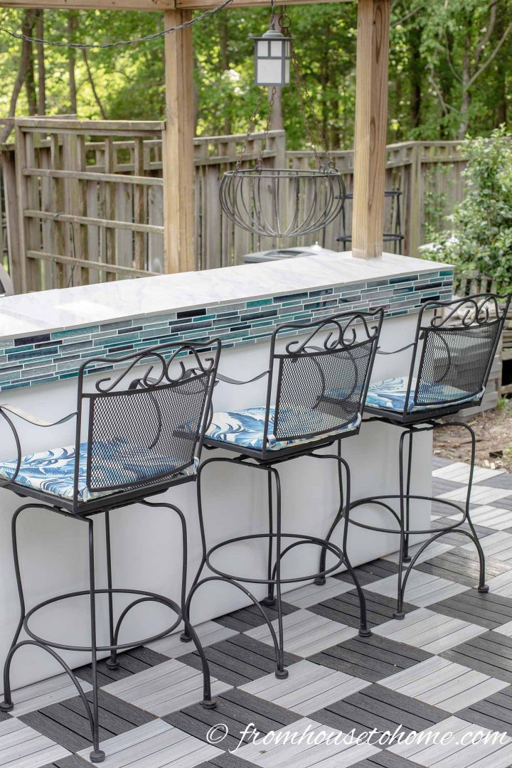 Outdoor bar with tile countertop, chairs with blue and white cushions and black and white checkered deck tile floor