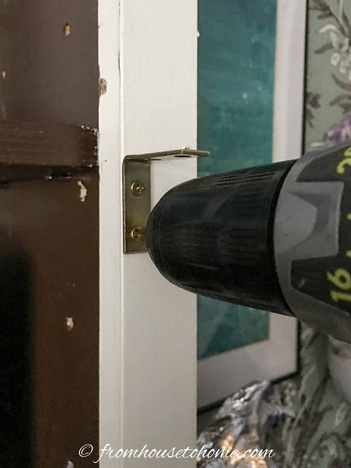 Cordless drill installing corner bracket for DIY TV frame