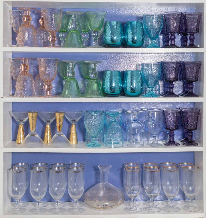 Multi-colored glass collection on white shelves