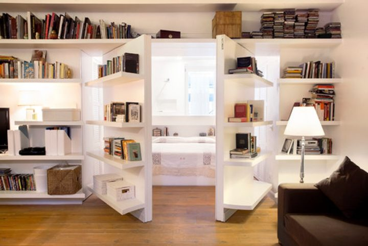 Contemporary home library bookshelves used as doors to bedroom
