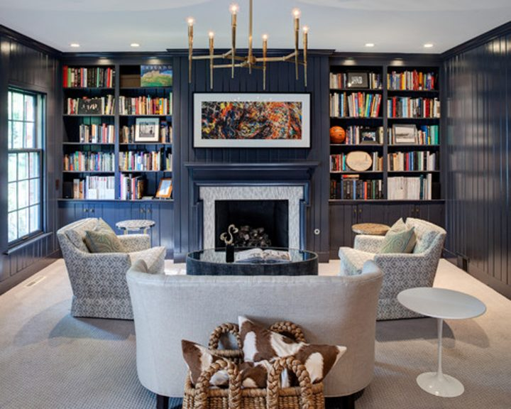 Blue and white living room with home library built around the fireplace