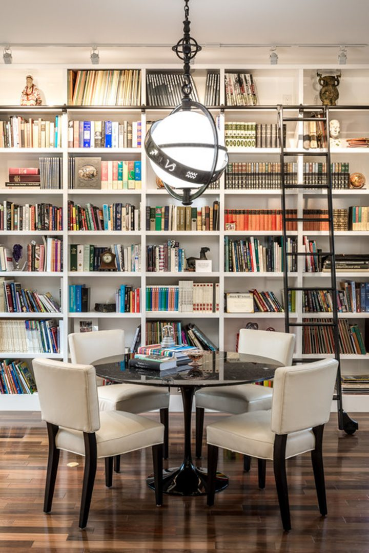 Dining room library with a wall of bookshelves and a ladder