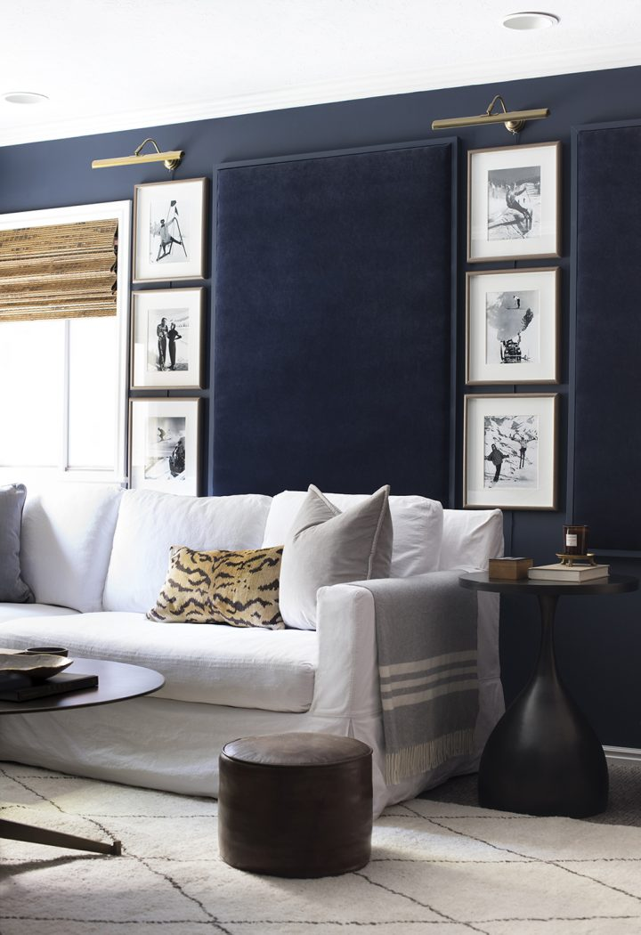 Navy blue basement painted in Sherwin Williams 2020 color of the year 'Naval'  with white sofa and gold accents