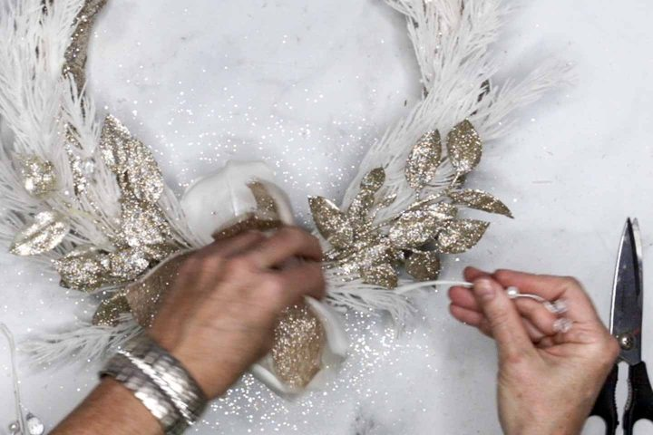 White pearl pick being added to a DIY wreath